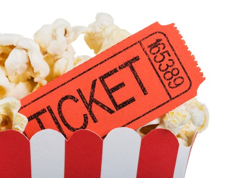 Concept of movie time. A movie ticket close up in a box of popcorn isolated on white background