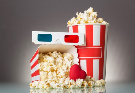 Bright box with popcorn, 3D glasses and a heart on a gray background Stock Photo
