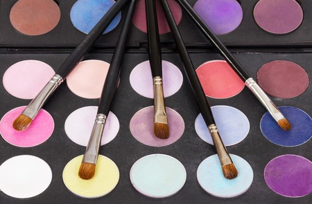 Bright eye shadow and cosmetic brushes. Background. Stock Photo