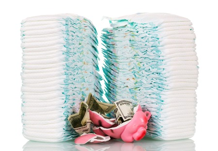 Piles of children's disposable diapers, broken piggy bank and money isolated on white background. Archivio Fotografico