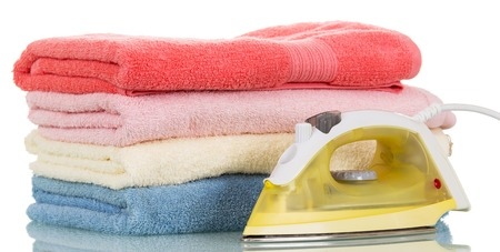 ironed: Steam iron and ironed colored towels isolated on white background.
