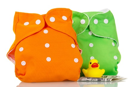 Modern eco-friendly diapers, money, and a rubber duck isolated on white background.