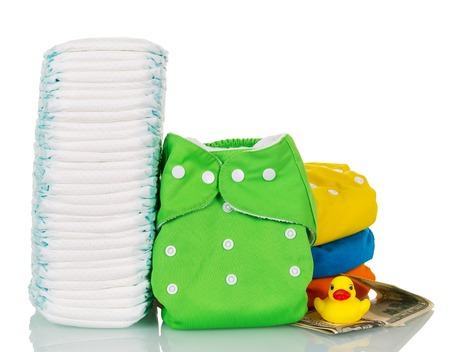 washable: Stack of disposable and cloth diapers, money, and a rubber duck isolated on white background.