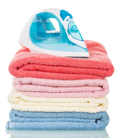 vapore acqueo: Steam iron and ironing colored towels isolated on white background.