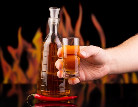 man's: A bottle, a glass of pepper vodka in a mans hand and a hot red pepper on a background of flames. Stock Photo