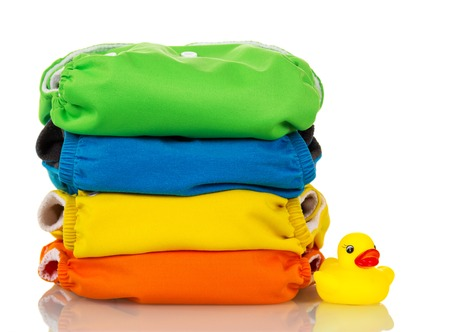 Organic cloth diapers and rubber duck isolated on white background.