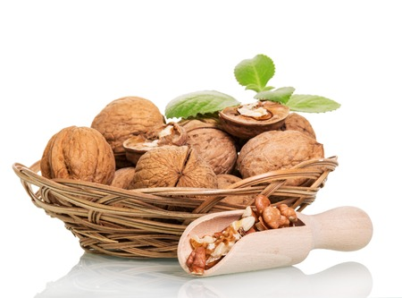 kernel: Walnuts in a wicker basket and kernel in the scoop isolated on white background.