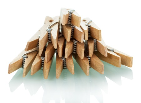 sprung: Pile of wooden clothespins isolated on white background. Stock Photo