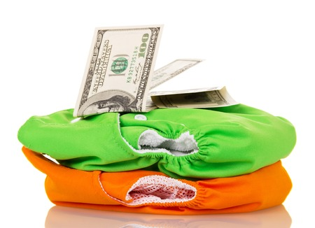 Modern eco-friendly diapers and money isolated on white background.