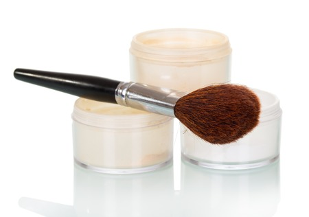 Cosmetic brush and powder jar of face isolated on white background. Stock Photo