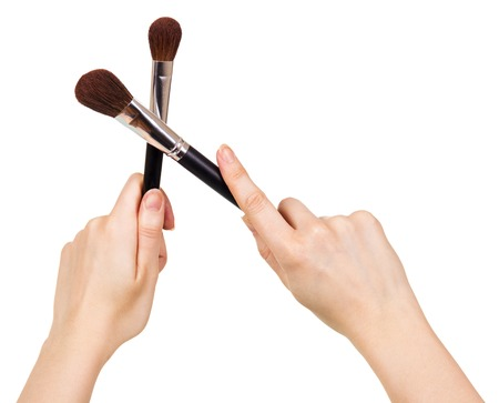 grooming product: Cosmetic brushes for a make-up in female hands isolated on white background.