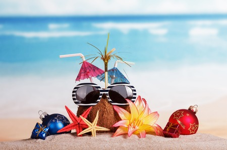 Coconut with sunglasses, starfish and Christmas balls, gifts in the sand against the sea