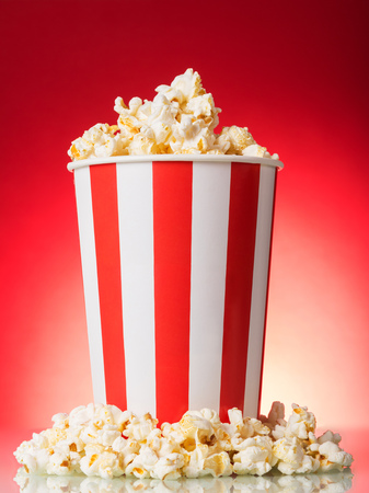 Salty popcorn in a large striped box on a bright red background Foto de archivo