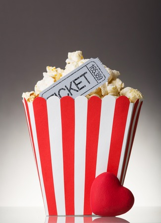 Large paper cup of popcorn and red heart on a gray background