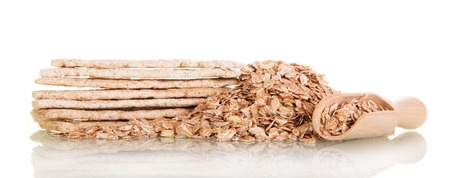 gritting: Rolled oats in a wooden spoon and cookies isolated on white background. Stock Photo