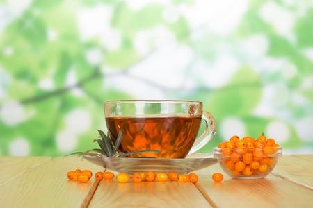 argousier: Un bol de baies d'argousier et une tasse de thé sur le fond vert abstrait. Banque d'images