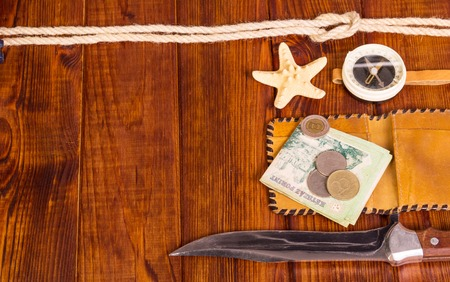 Old, compass, money, a knife and a starfish on a background of dark wood. Stock Photo