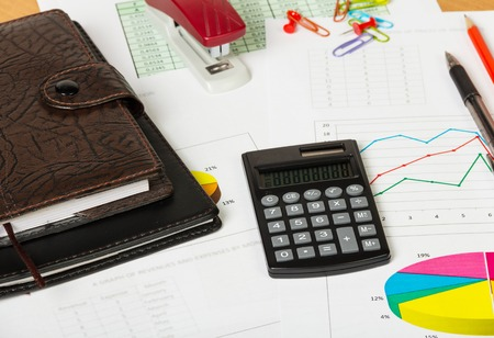 stationery items: Notebooks, calculator and various stationery items on the desktop background. Stock Photo