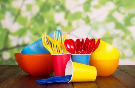 밝은 플라스틱 식기 : 그릇, 포크, 숟가락 및 컵 추상적 인 녹색 배경에.