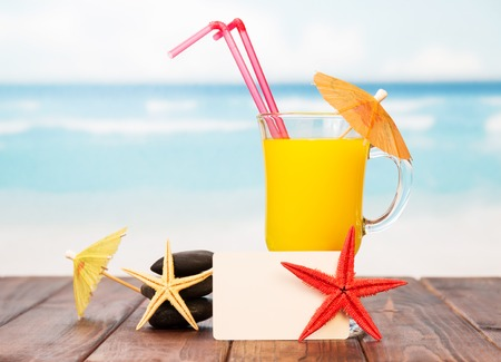 Blank card, a glass of orange cocktail and a starfish on a background of the sea. Stock Photo
