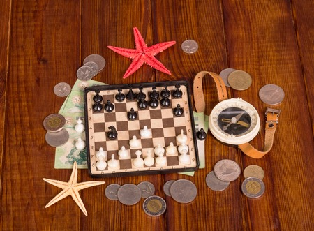 monete antiche: Accessories for the traveler: chess, compass, money and starfish on a background of dark wood.