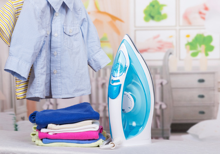 Steam iron and clothes on a background of a childs room. Stock Photo
