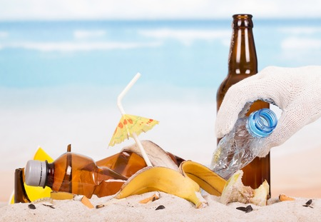 food waste: Glass bottle and plastic, food waste in the sand against the sea. Stock Photo