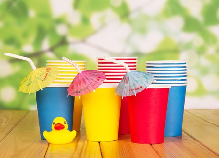 Multi-colored paper cups, straws and rubber duck on a green abstract background.