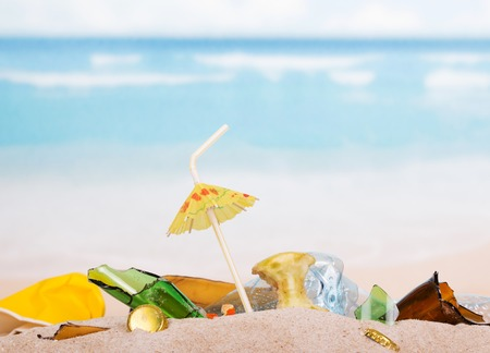 Food and household waste in the sand against the sea.