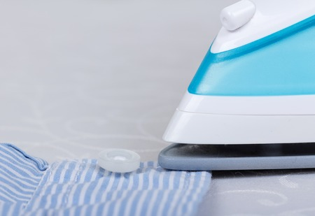 creased: Shirt ironing using a steam iron on a light gray background.