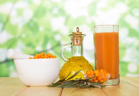 Buckthorn berries, oil bottle and a glass of juice on the abstract green background. Stock Photo