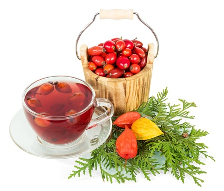 briar: Wooden bucket with berries of wild rose and cup of tea isolated on white background. Stock Photo