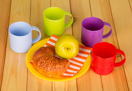 bar ware: Bright cups and disposable plate with a croissant and an apple on a background of light wood.