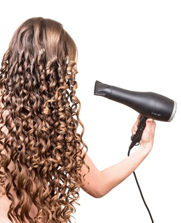 hairdryer: Girl with curly hair holding a hairdryer isolated on a white background. Stock Photo