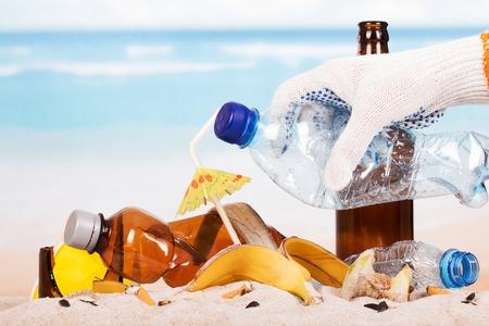 모래 배경에서 쓰레기 더미에 플라스틱 병을 들고 손을.