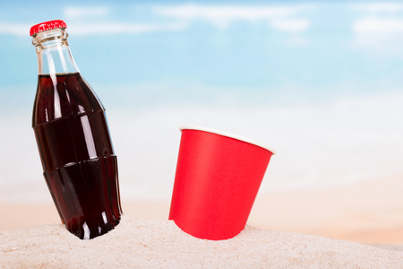 Bottle with a refreshing drink and a disposable cup of in the sand on the seashore.