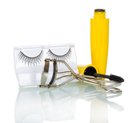 Black false eyelashes, mascara and hair curlers isolated on white background.