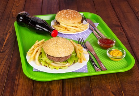 coke bottle: Hamburger with cheese, meatballs, salad, fries and a Coke bottle on the background of dark wood. Stock Photo
