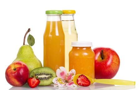 Baby food, puree and fruit juices in glass bottles isolated on white background.