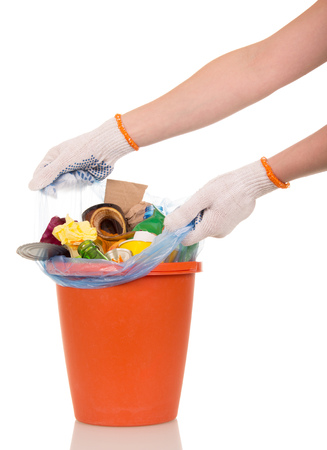 crushed cans: Womens hands are removed from the bucket bag with household waste isolated on white background. Stock Photo