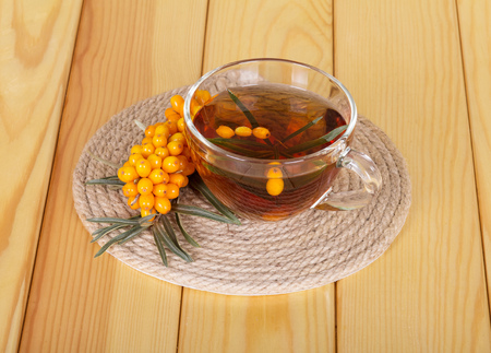 Bunch of sea buckthorn and cup of tea on a background of light wood. Stockfoto