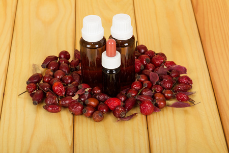 complementary: Hips and bottles of essential oil on a background of light wood. Stock Photo