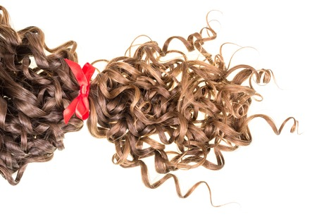 Brown wavy hair tied red ribbon isolated on white background. Stock Photo