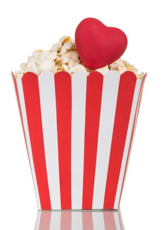 Popcorn in a striped paper box and a red heart isolated on white background