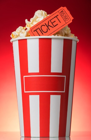 Large striped popcorn box with orange a ticket to the movies on a bright red background Stock Photo