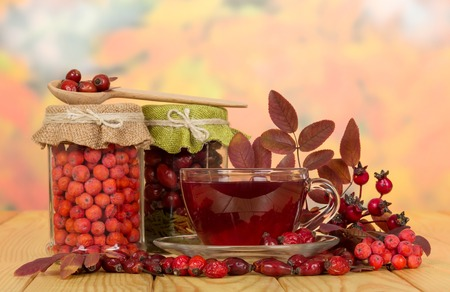 briar: In glass jars rosehip berries, mountain ash and a cup of tea on a background of autumn leaves. Stock Photo