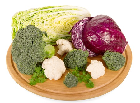 Set of different types of fresh cabbage on a round wooden board isolated on white background.