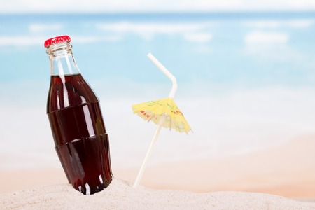 A bottle of cola in the sand on the seashore.