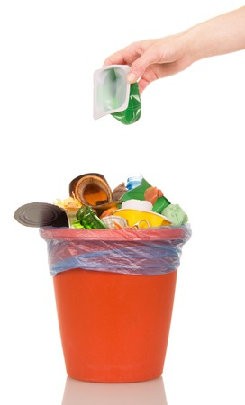Female hand putting a plastic cup into a bucket of household waste isolated on white background. Stock Photo