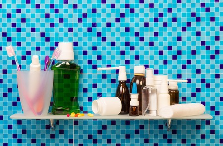 Shelf with toiletries and cosmetics on background bathroom. Stock Photo